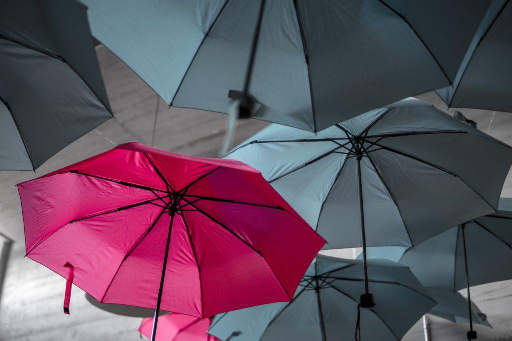 Pink Umbrella Amongst Grey Umbrellas